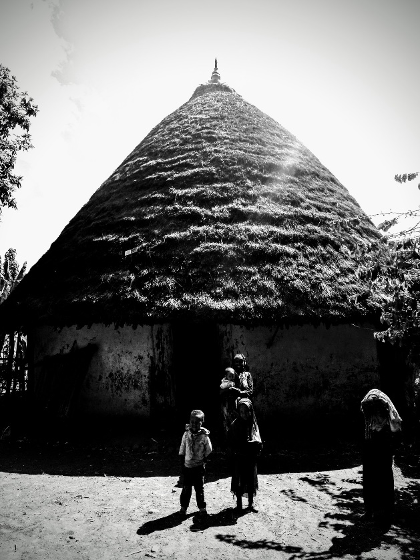 """Tukul"" (traditional house) in Butajira area with mother and children. The livestock is kept inside, where people also cook and sleep"